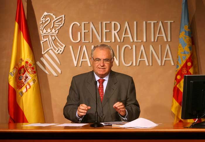 En la imagen Juan Cotino sentado en rueda de prensa y tras él el frontis de la Generalitat Valenciana y a ambos lados de izquierda a derecha la bandera de España y la bandera de la Comunidad Valenciana